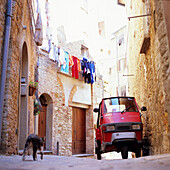 Small car standing in a narrow alley, Montepulciano, Tuscany, Italy