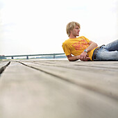Young blond man lying on jetty at Rhine River, Germany