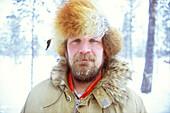 Portrait of a man with frozen beard in snowy forrest, Lappland, Sweden
