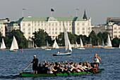 Big canoe on Inner Alster Lake, Atlantic Hotel in the background, Hamburg, Germany