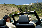 Tourists sitting in a convertible in front of the Hollywood sign, emblem, Los Angeles, L.A., Caifornia, U.S.A., United States of America