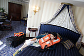 Woman with life vest in a suite, Cruise ship MS Delphin Renaissance
