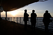 People standing at the railing at sunset, cruise ship MS Delphin Renaissance