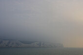 Limestone cliffs at the English Channel on a foggy morning, view from cruise ship MS Delphin Renaissance