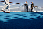 Passengers standing at the railing in the sunlight, cruise ship MS Delphin Renaissance