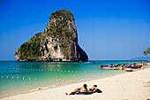 Tourists lying at white sandy beach, overgrown chalk cliff in background, Phra Nang Beach, Laem Phra Nang, Railay, Krabi, Thailand, after the tsunami