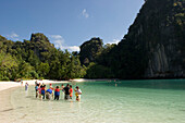 Group of tourists standing in shallow water at beach of Koh Hong, Hong Island, Krabi, Thailand