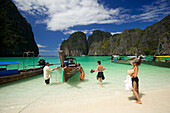 """Tourists next to anchored boats in the Maya Bay, a beautiful scenic lagoon, famous for the Hollywood film """"The Beach"""", Ko Phi-Phi Leh, Ko Phi-Phi Islands, Krabi, Thailand, after the tsunami"""