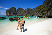 "A young couple walking over the beach, anchored boats in background, Maya Bay, a beautiful scenic lagoon, famous for the Hollywood film ""The Beach"", Ko Phi-Phi Leh, Ko Phi-Phi Islands, Krabi, Thailand, after the tsunami"