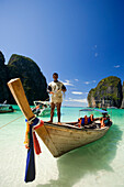 """Boatman standing on a long tail boat and holding a rope, Maya Bay, a beautiful scenic lagoon, famous for the Hollywood film """"The Beach"""", Ko Phi-Phi Leh, Ko Phi-Phi Islands, Krabi, Thailand, after the tsunami"""