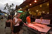 Two women in front of a fish restaurants, Ko Phi Phi Don, Ko Phi Phi Island, Krabi, Thailand, after the tsunami
