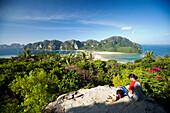Woman and two cats sitting on Viewpoint, view to Ao Lo Dalam and Ao Ton Sai, Ko Phi Phi Don, Ko Phi Phi Island, Krabi, Thailand