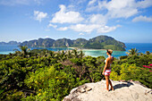 Young woman standing on Viewpoint and looking to Ao Lo Dalam and Ao Ton Sai, Ko Phi Phi Don, Ko Phi Phi Island, Krabi, Thailand