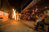Tourists sitting in a beach bar, man juggling fire pois, Ko Phi Phi Don, Ko Phi Phi Island, Krabi, Thailand, after the tsunami