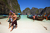 "Tourists leaving long tail boats, Maya Bay, a beautiful scenic lagoon, famous for the Hollywood film ""The Beach"", Ko Phi-Phi Leh, Ko Phi-Phi Islands, Krabi, Thailand, after the tsunami"