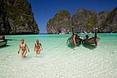 "Two young women wearing bikini walking through shallow water, Maya Bay, a beautiful scenic lagoon, famous for the Hollywood film ""The Beach"", Ko Phi-Phi Leh, Ko Phi-Phi Islands, Krabi, Thailand, after the tsunami"
