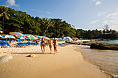 Three girls walking over Laem Singh Beach, between Hat Surin and Hat Kamala, Phuket, Thailand, after the tsunami