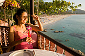 Young woman sitting on terrace of Baan Rim Pa restaurant and enjoying the stunning ocean view, Patong Beach, Hat Patong, Ao Patong, Phuket, Thailand, after the tsunami