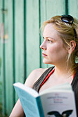 Woman leaning on boathouse, reading a book, Germany