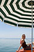 Bayern, Deutschland, Starnberg, Starnberger See, Frau mit Ipod, Leoni, Elektroboot, Sonnenschirm, See, Frau, sonnig, wolkenlos, blauer Himmel, blond