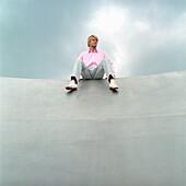 sitzender Mann, Deutscher, rosa Hemd, stylisch, modern, Turnschuhe, blond, sitzt auf Mauer, oben sitzen, Hochsitz, hochsitzen, Aussicht, Ðbersicht, Wolkenhimmel, Regenwolken