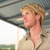 Blond man standing under a roof, Germany