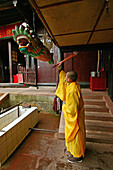 Monk beating on wooden fish, call for prayer, Xixiang Chi monastery, Emei Shan, Sichuan province, China, Asia