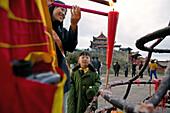 Frau und Kind zünden morgens eine Kerze an, Emei Shan Gebirge, Provinz Sichuan, China, Asien