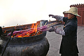 Man burning incense sticks in a cauldron, Emei Shan mountains, Sichuan province, China, Asia