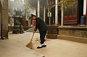 A nun sweeping the courtyard of Xuandu monastery, Heng Shan South, Hunan province, China, Asia