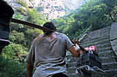 Porter carrying building material up steep mountain steps, Hua Shan, Shaanxi province, China, Asia