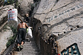 porter, porters carry furniture and building material on their back up steep mountain steps, Taoist mountain, Hua Shan, Shaanxi province, Taoist mountain, China, Asia