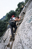 photographer Karl Johaentges with backpack and camera bag, vertical stone cliffs, Taoist mountain, Hua Shan, Shaanxi province, Taoist mountain, China, Asia