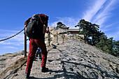 Fish Back Ridge, pilgrim path along stone steps with worn down chain handrail to South Peak Monastery, western tourist with backpack, Hua Shan, Shaanxi province, Taoist mountain, China, Asia