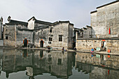 women washing in village pond, part of a complex water system, where water is channelled in front of every house, Hongcun, Huangshan, ancient village, living museum, China, Asia, World Heritage Site, UNESCO