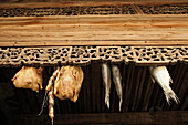 Artful carvings and dryed food at the roof beam of a house in Hongcun, Huang Shan, China, Asia