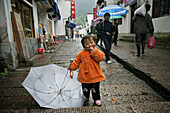 Little girl with umbrella at an alley at the village Jiuhuashan, Anhui province, China, Asia
