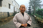 A nun standing in front of monastery of the village minyuan, Jiuhua Shan, Anhui province, China, Asia
