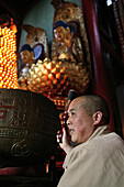 A monk at prayer service at Qiyuan monastery, Jiuhuashan, Anhui province, China, Asia