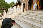 Pilgrims bowing on the stairs in front of Ronshen monastery, Jiuhuashan, Anhui province, China, Asia