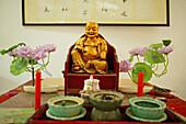 dining hall altar with Buddha statue and plastic lotus flowers, Jiuhua Shan Village, Monastery, Jiuhuashan, Mount Jiuhua, mountain of nine flowers, Jiuhua Shan, Anhui province, China, Asia