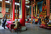 People at prayer hall of the Wangfo Monastery, Jiuhuashan, Anhui province, China, Asia