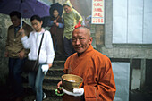 A mendicant and tourists in front of Longevity monastery, Jiuhua Shan, Anhui province, China, Asia