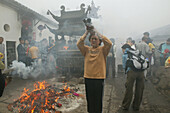 Pilgrims burning incense sticks in front of Longevity monastery, Jiuhua Shan, Anhui province, China, Asia