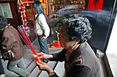 pilgrim woman praying offering incense sticks, Jiuhuashan, Mount Jiuhua, mountain of nine flowers, Jiuhua Shan, Anhui province, China, Asia