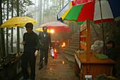 Pilgrims in the rain on the pilgrimage route, Jiuhua Shan, Anhui province, China, Asia