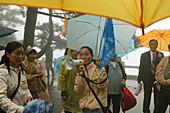 A group of pilgrims standing in the rain, Jiuhua Shan, Anhui province, China, Asia