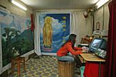 Young woman sitting on a foot warmer Huo Tong at a photo studio, Jiuhua Shan, Anhui province, China, Asia