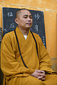 Praying monk at Avalokiteshvara monastery, Jiuhua Shan, Anhui province, China, Asia