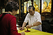 for a donation the pilgrims get a block print of the temple's name on their yellow bag, offical seal, Buddhist Island of Putuo Shan near Shanghai, Zhejiang Province, East China Sea, China, Asia